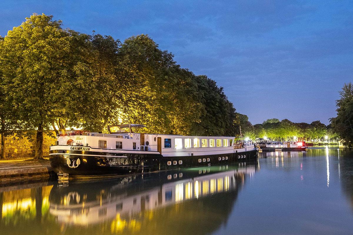 C'est La Vie Luxury Hotel Barge docked in the evening